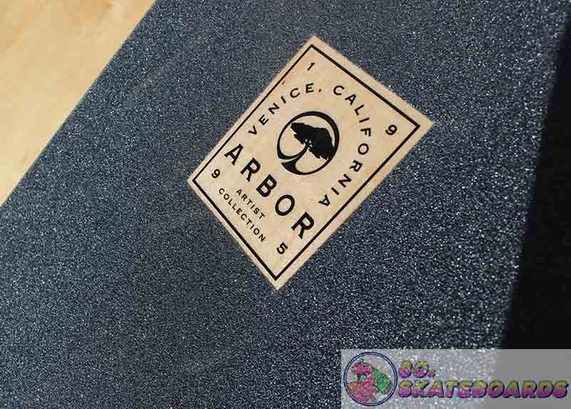 Arbor longboard review featuring Arbo icon pearing through griptape